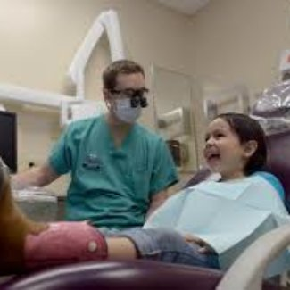 little girl sitting smiling in a dental chair